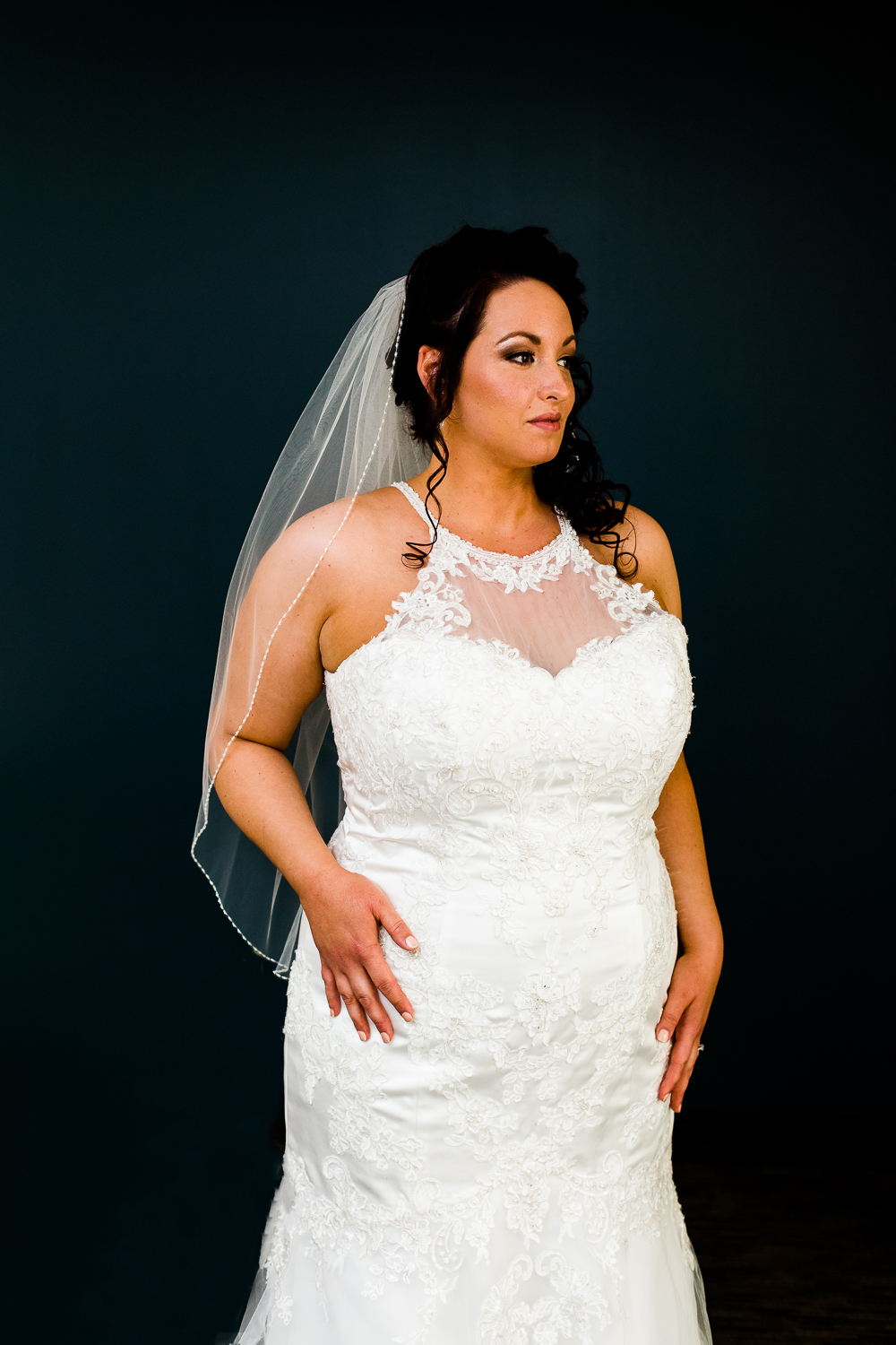 Bride in white halter gown with lacework. She is against a blue background looking off into the distance.