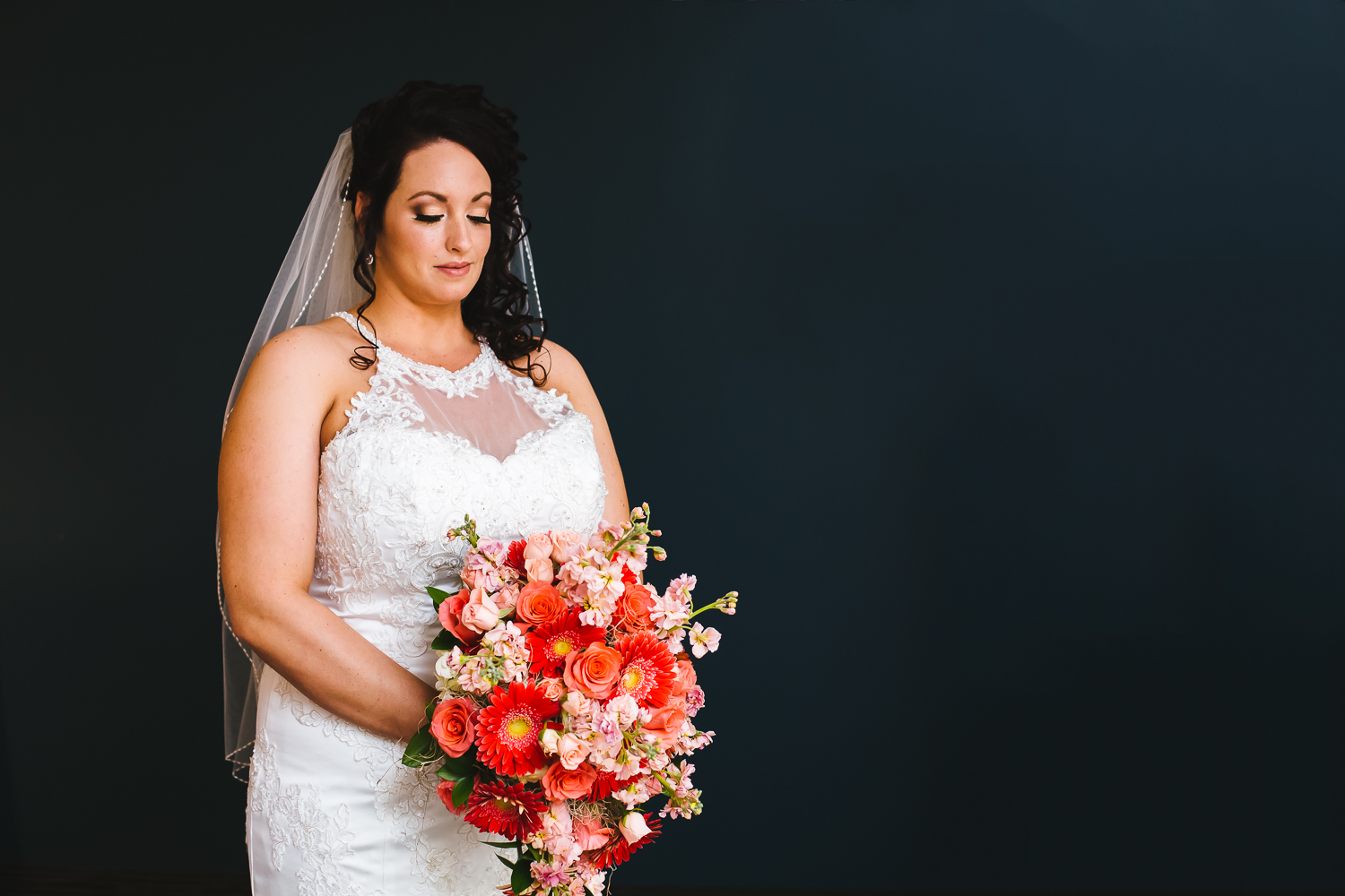 Bride looks down at giant bouquet of coral flowers. She is in a white gown. Her hair has curls. She has a veil on.