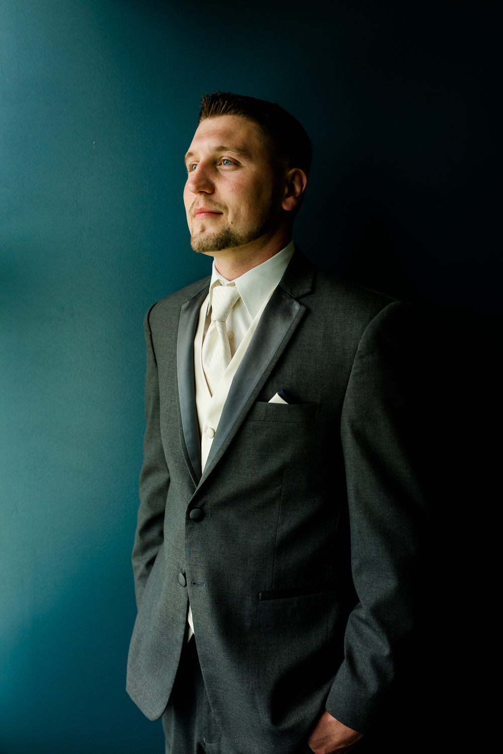 Portrait of a groom against a blue background. He is looking away from the camera.