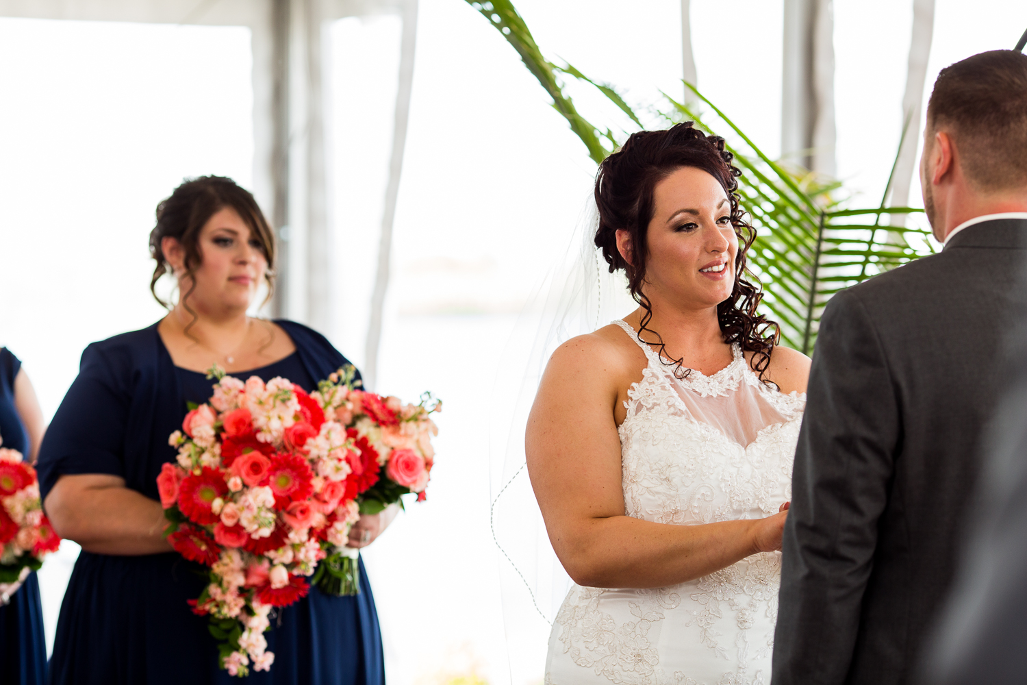 Bride looks at groom and says vows during wedding ceremony.