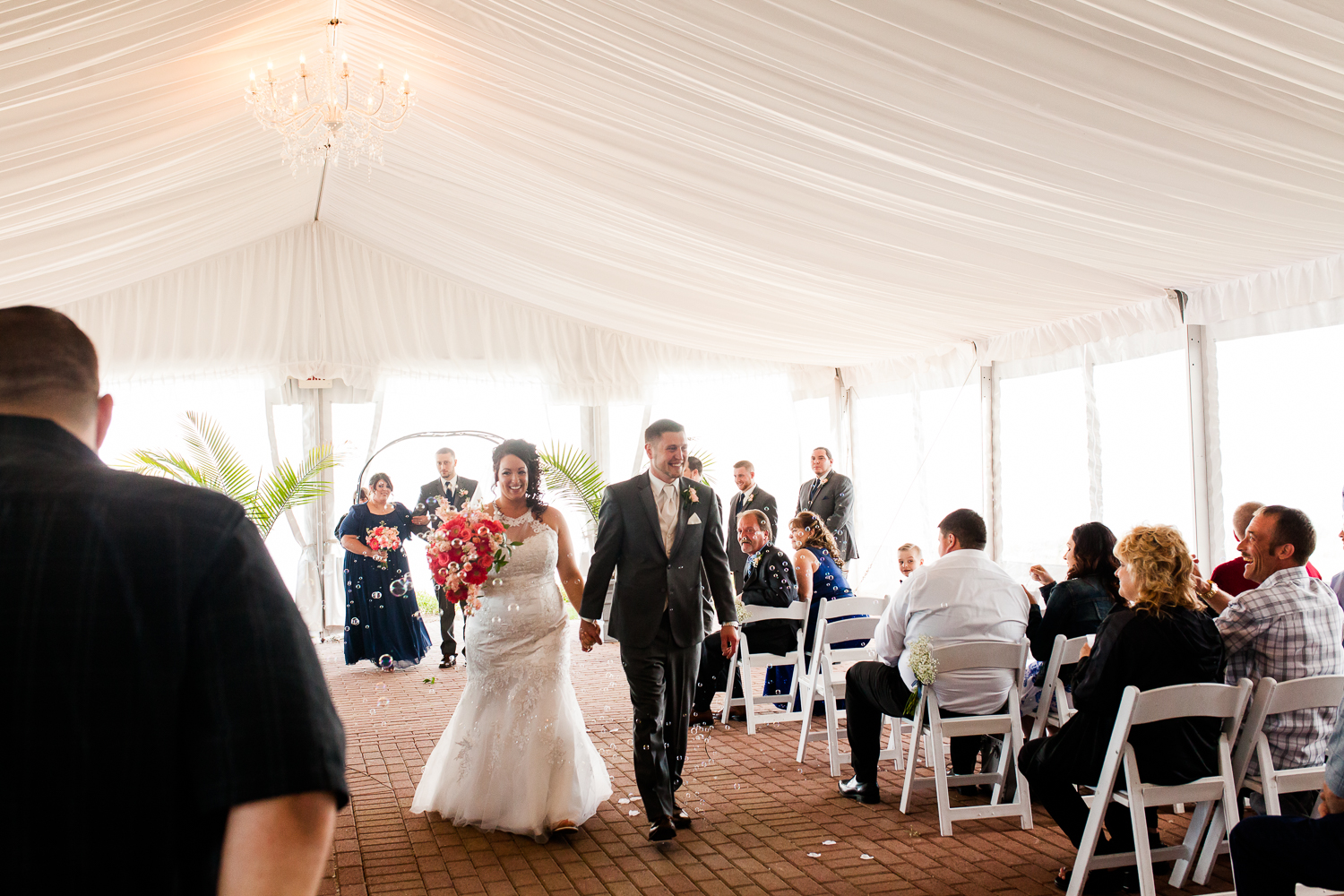 Bride and groom walk back down the aisle after the ceremony. Guests blow bubbles at them.