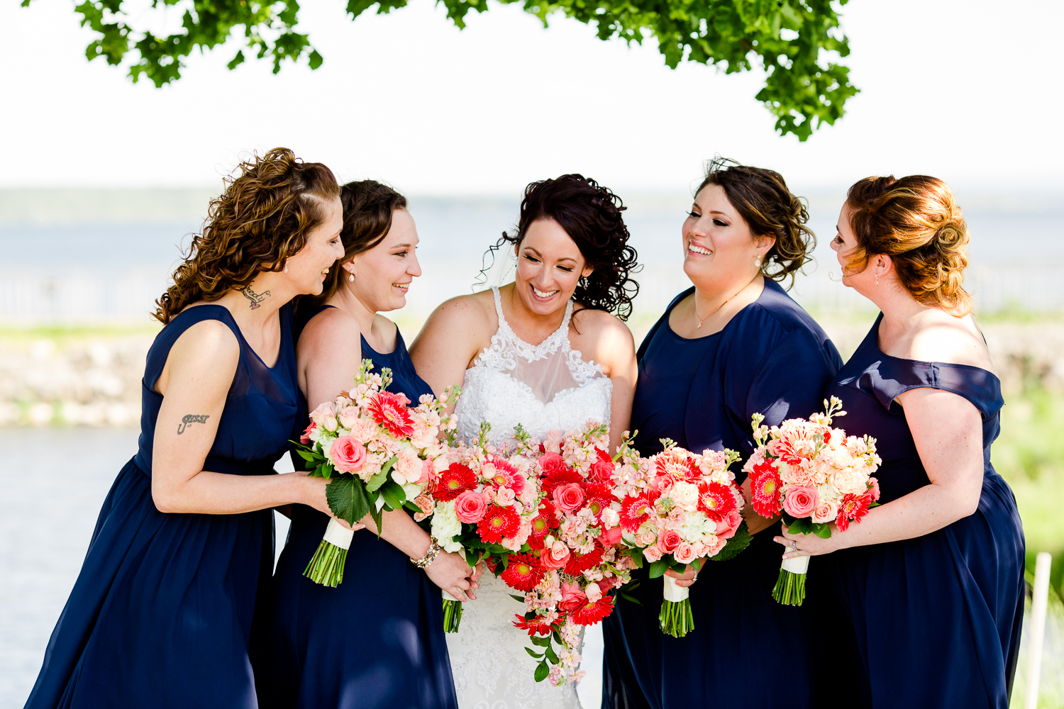 Bridesmaids wearing navy blue dresses surround a bride in a white gown. They have coral flowers. They are laughing.