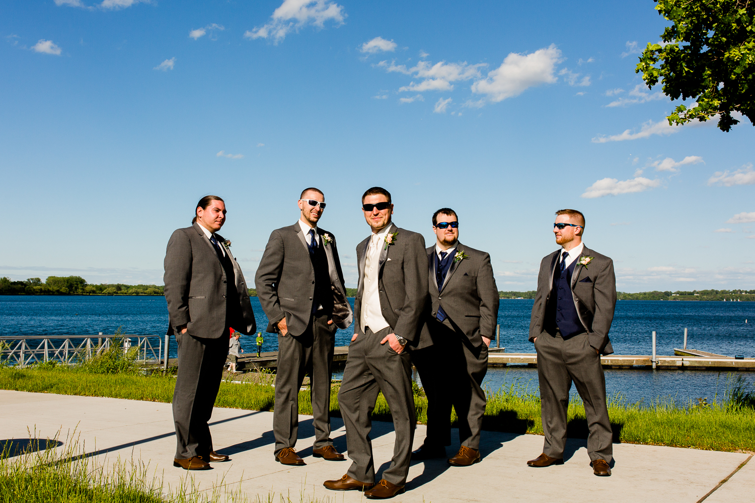 The groom and groomsmen have their backs to a lake. They are wearing sunglasses. There are clouds in the sky.