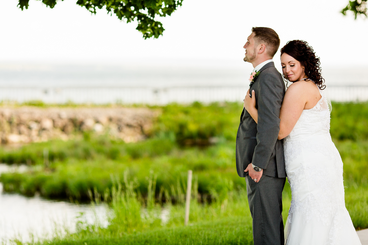 Bride holds groom from behind. Groom looks out into the distance. There is green grass behind them.