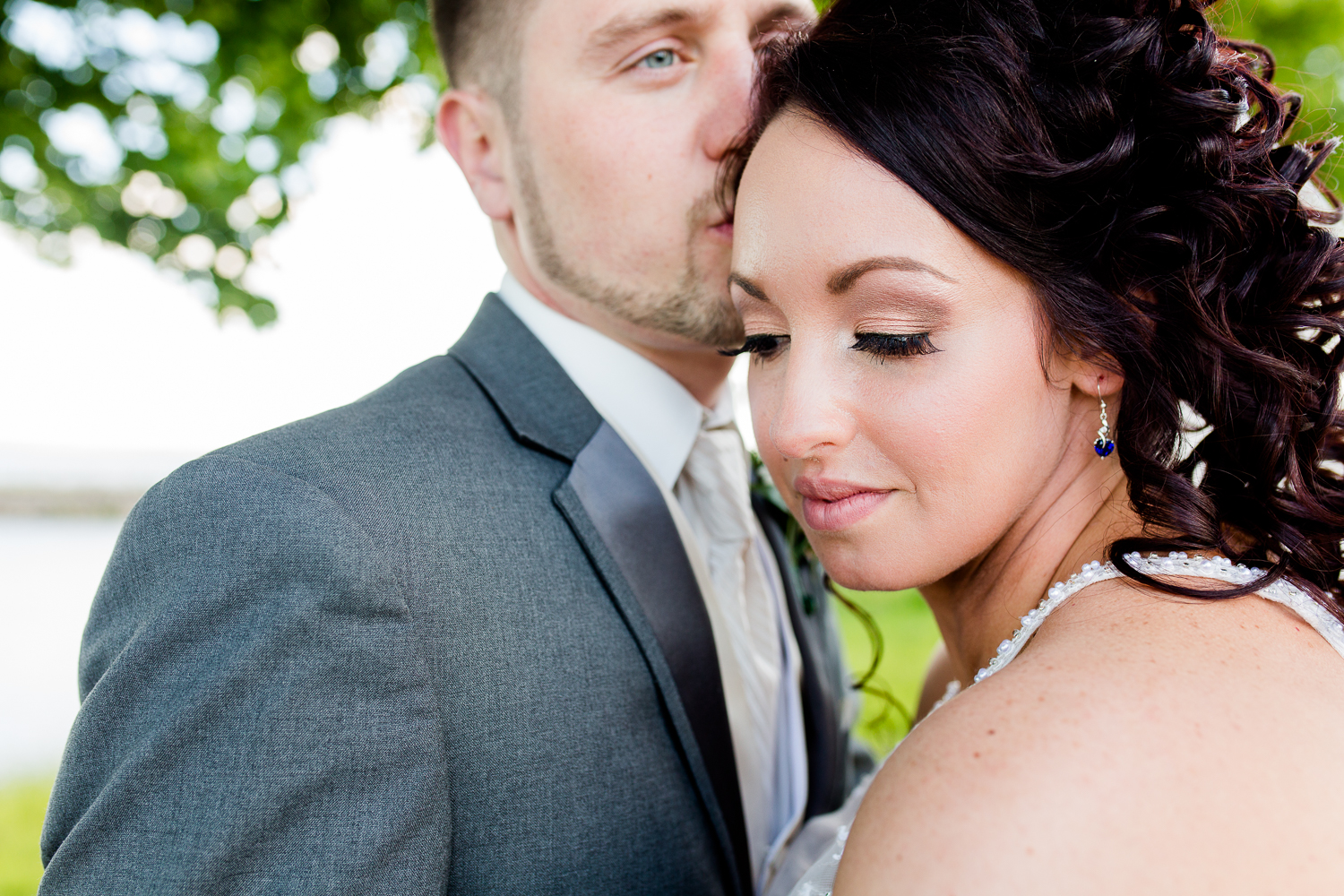 A close up of the bride's face. She has sapphire earrings on. The groom is kissing the side of her head.