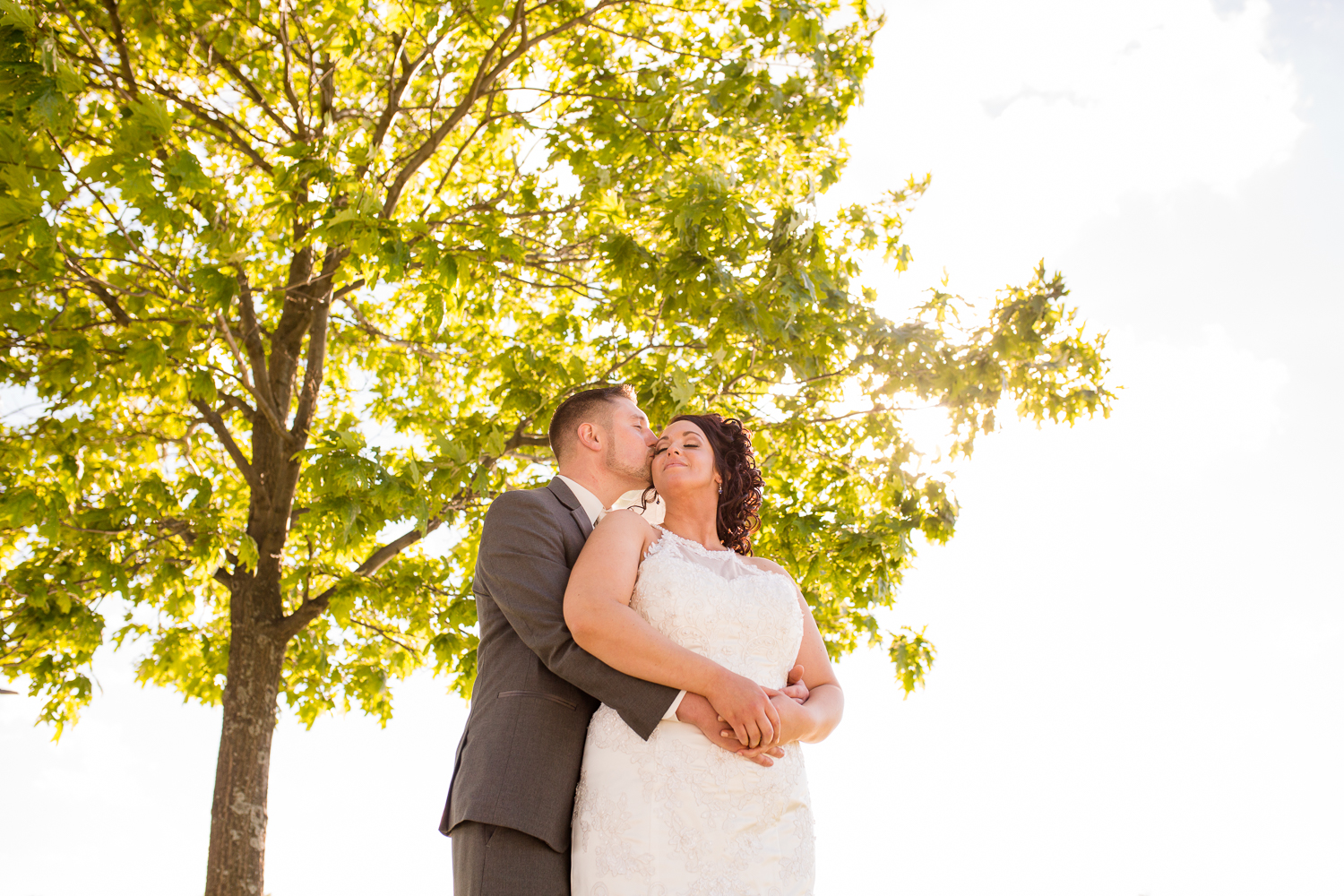 An image looking up at the bride and groom from below. There is a tree above them. The groom has his arms wrapped around the bride and is kissing her.