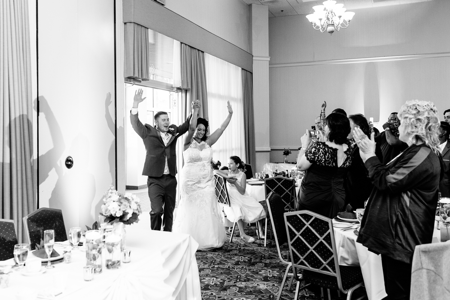A black and white image of the bride and groom entering the reception. They have their hands up in the air.