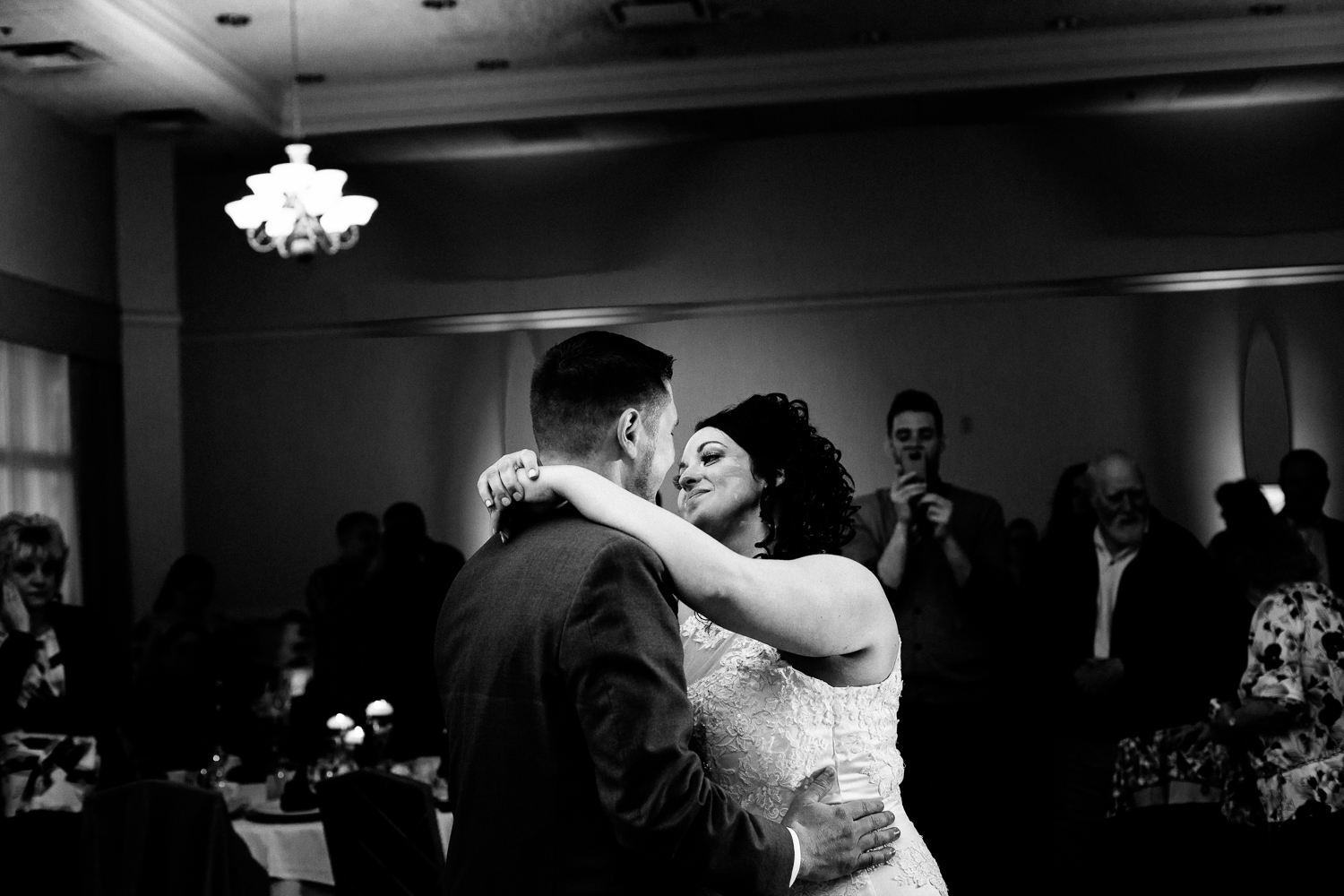 A black and white image of the first dance at a wedding. The bride is smiling at the groom.