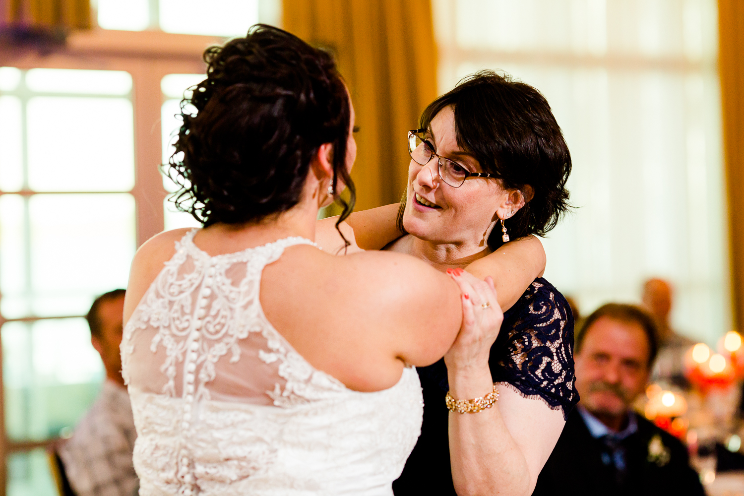 A mother daughter dance. The mother is smiling at her daughter. The back of the brides dress is covered in lace.