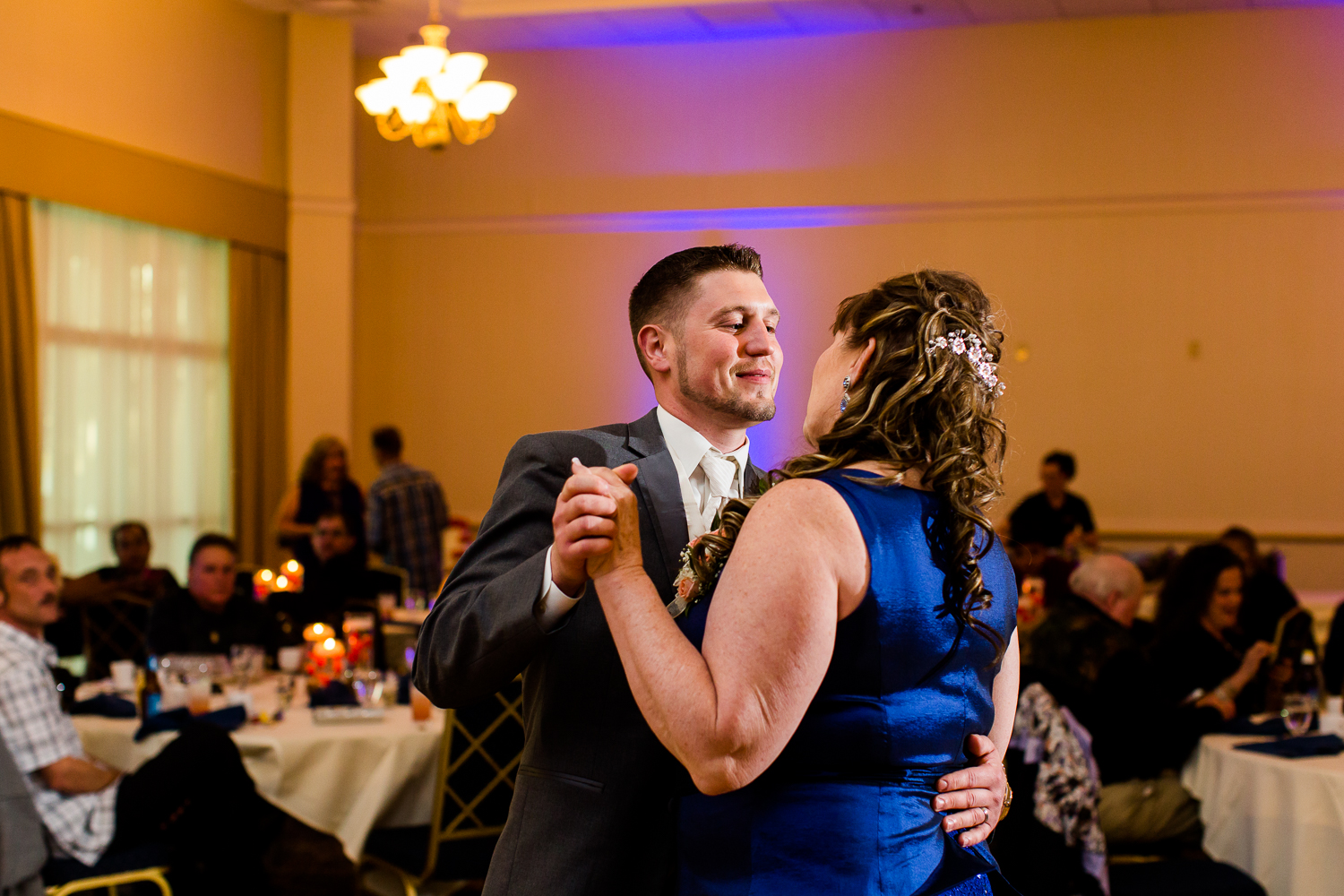 The groom looks fondly at his mother during the mother son dance at his wedding reception.