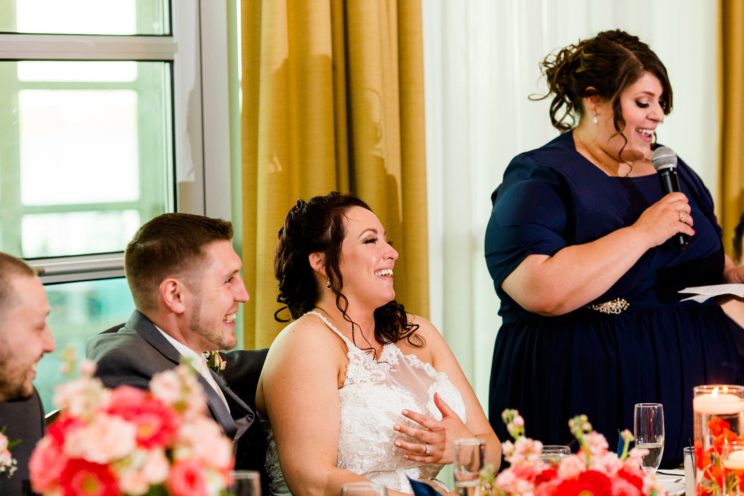 The bride laughs as her maid of honor delievers a toast.