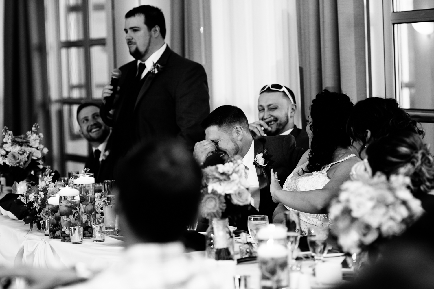 A black and white image of the groom laughing as a groomsman delievers a toast.