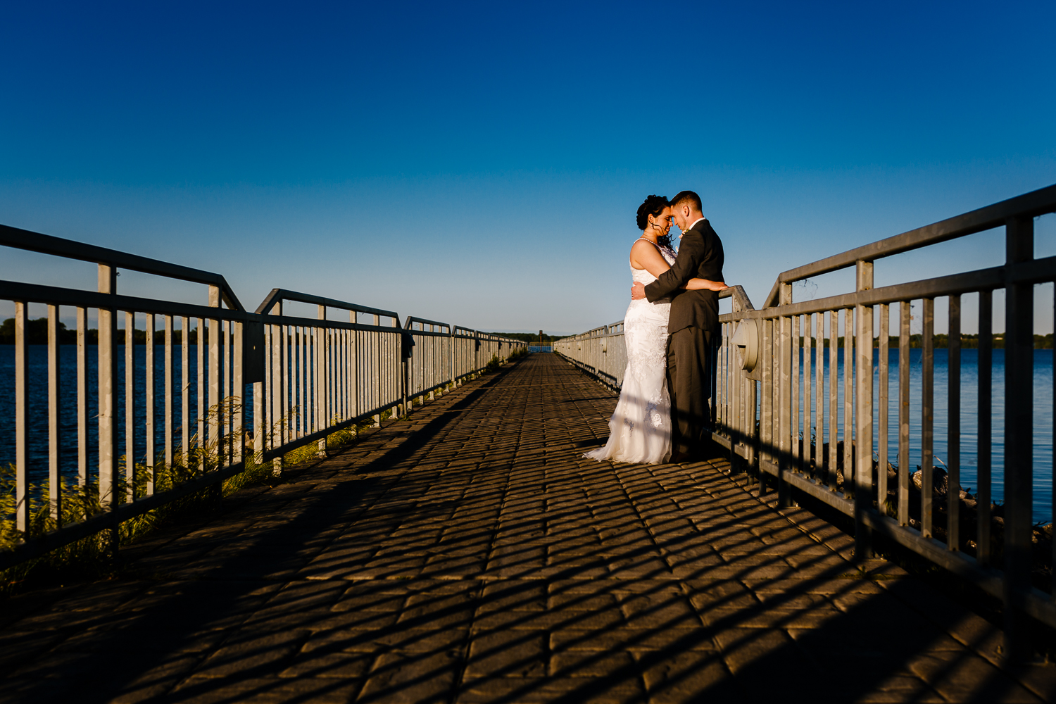 An image of the bride and groom on a pier at sunset. They are facing each other with their forheads touching.
