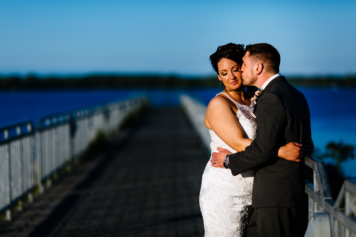 Groom kisses his bride on a pier at sunset. A blue lake is in the background.