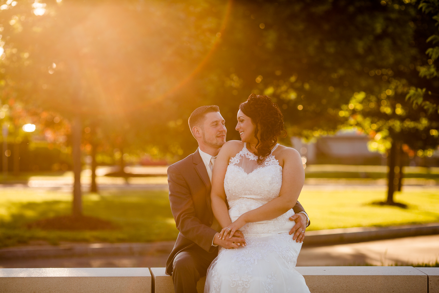 Bride and groom look at each other sweetly. There is sun flare in the image. The bride is sitting on the grooms lap.