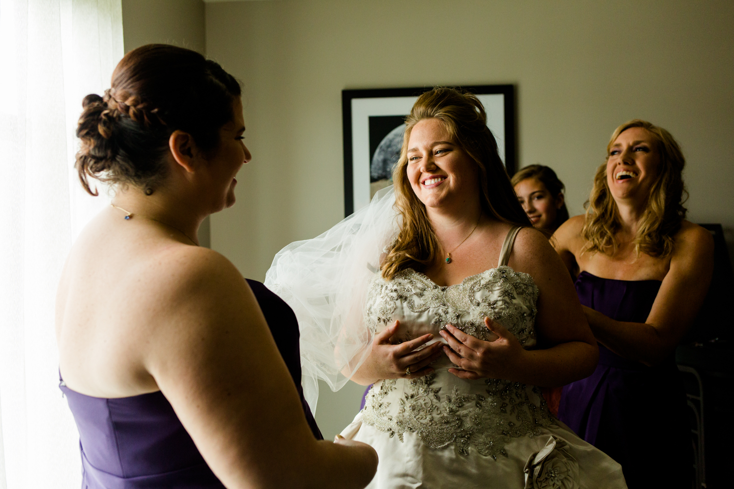 Bridesmaids help bride into her wedding gown. They are laughing and happy.