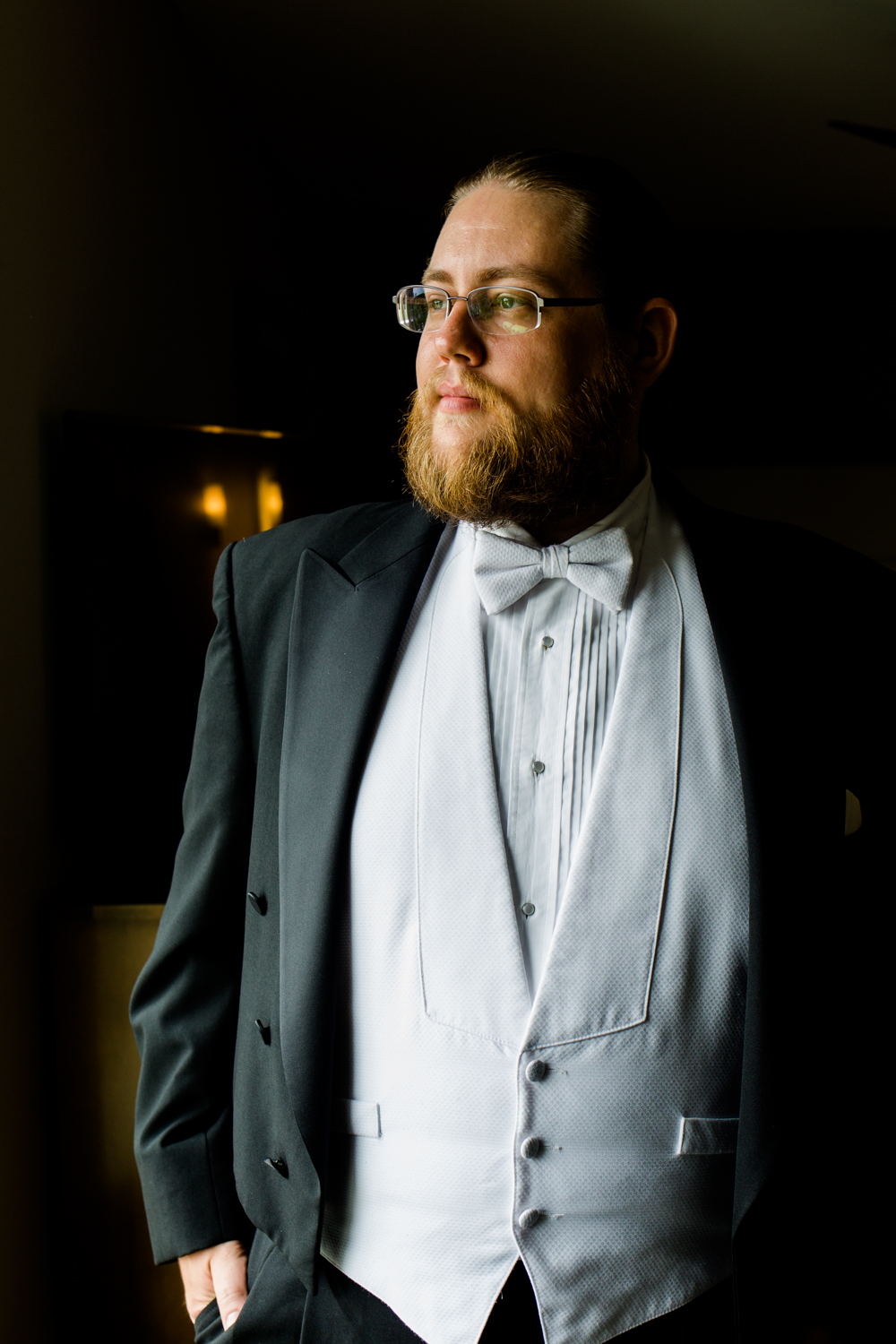 Portrait of a groom looking out a window. He has a black tux on with a white bowtie.