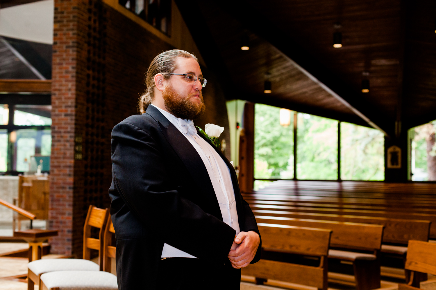 Groom watches his bride walk down the aisle in a church. He is emotional.