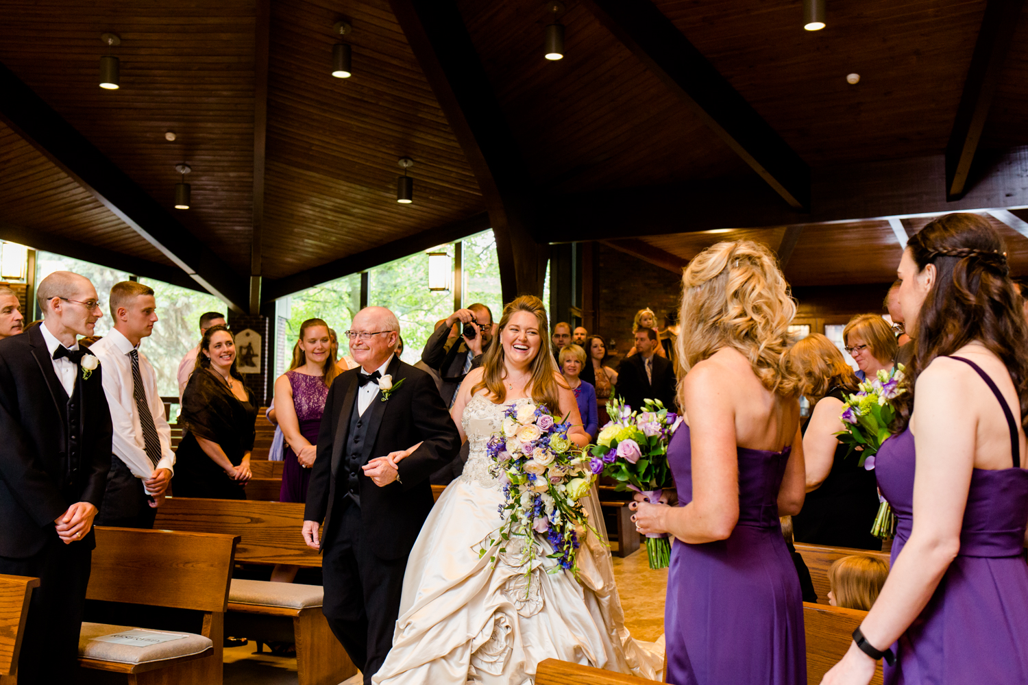 Bride walks down the aisle with her father. She is laughing and smiling at her bridesmaids. She is in a church.