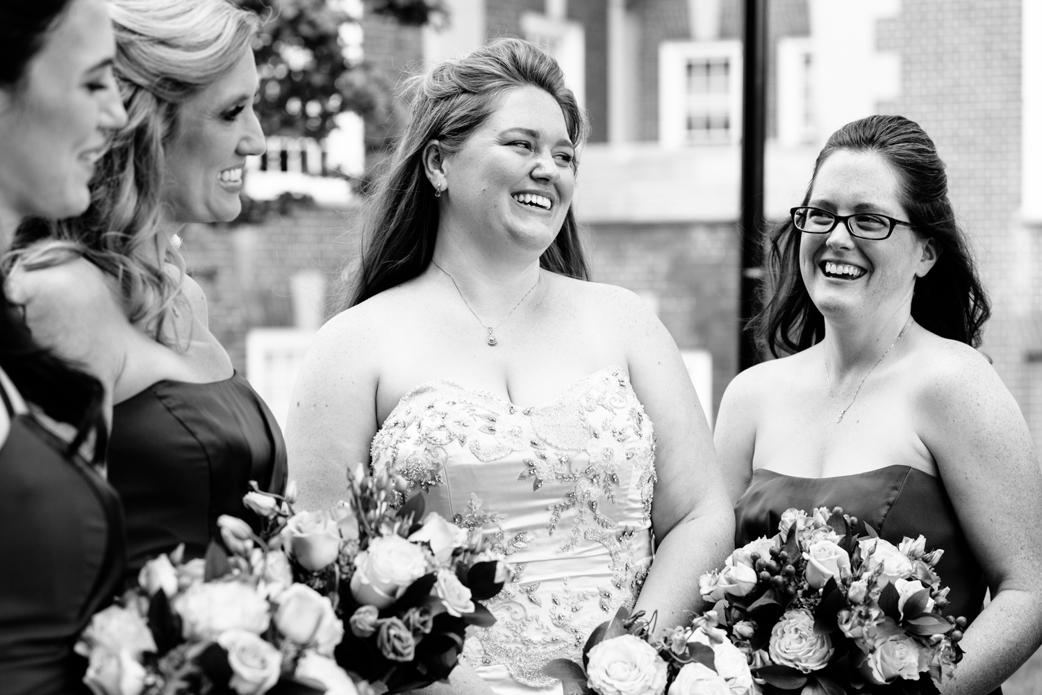 Black and white image of bride laughing with bridesmaids.