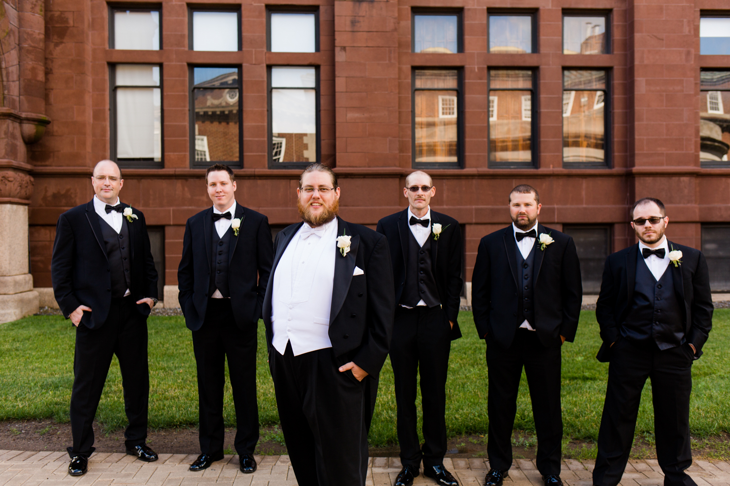 Groom in a tux with his groomsmen behind him.