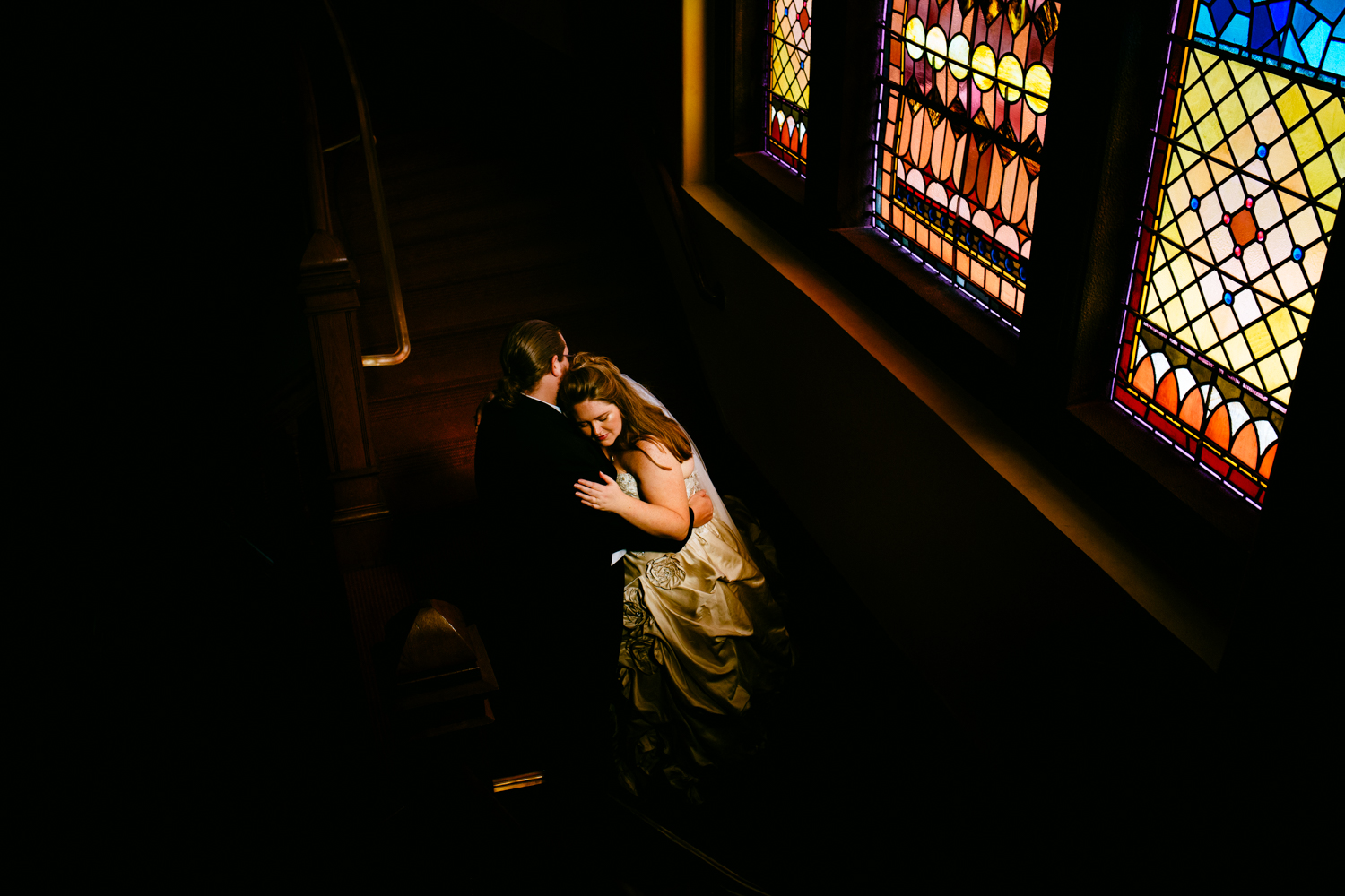 Moody portrait of bride leaning against groom. The background is dark except for a stainglassed window.