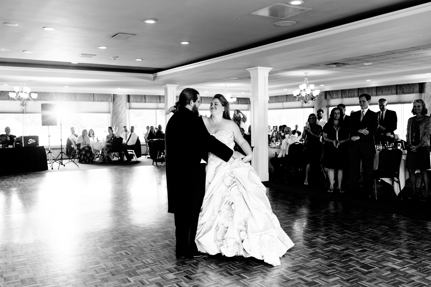 A black and white image of the bride and groom sharing their first dance.