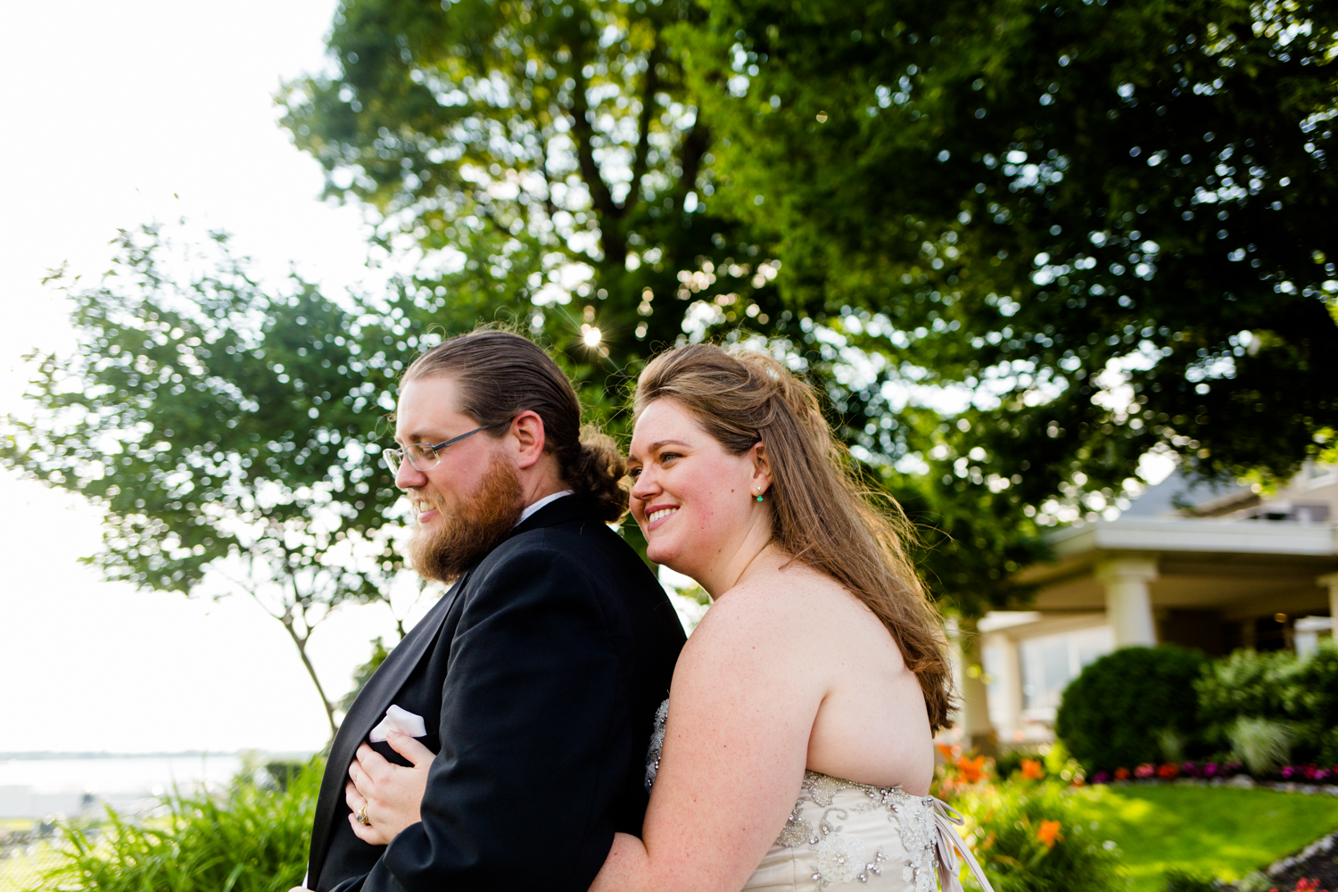 Portrait of bride hugging groom from behind. They are both smiling.