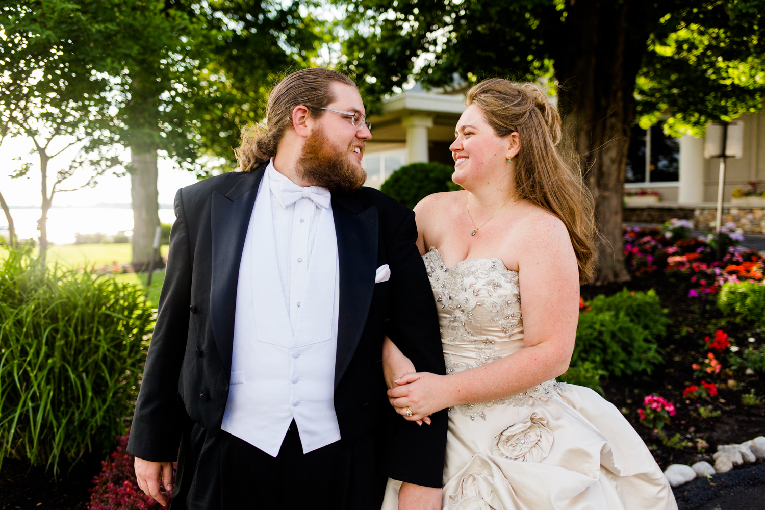 Portrait of bride and groom looking at each other. There are flowers in the background.