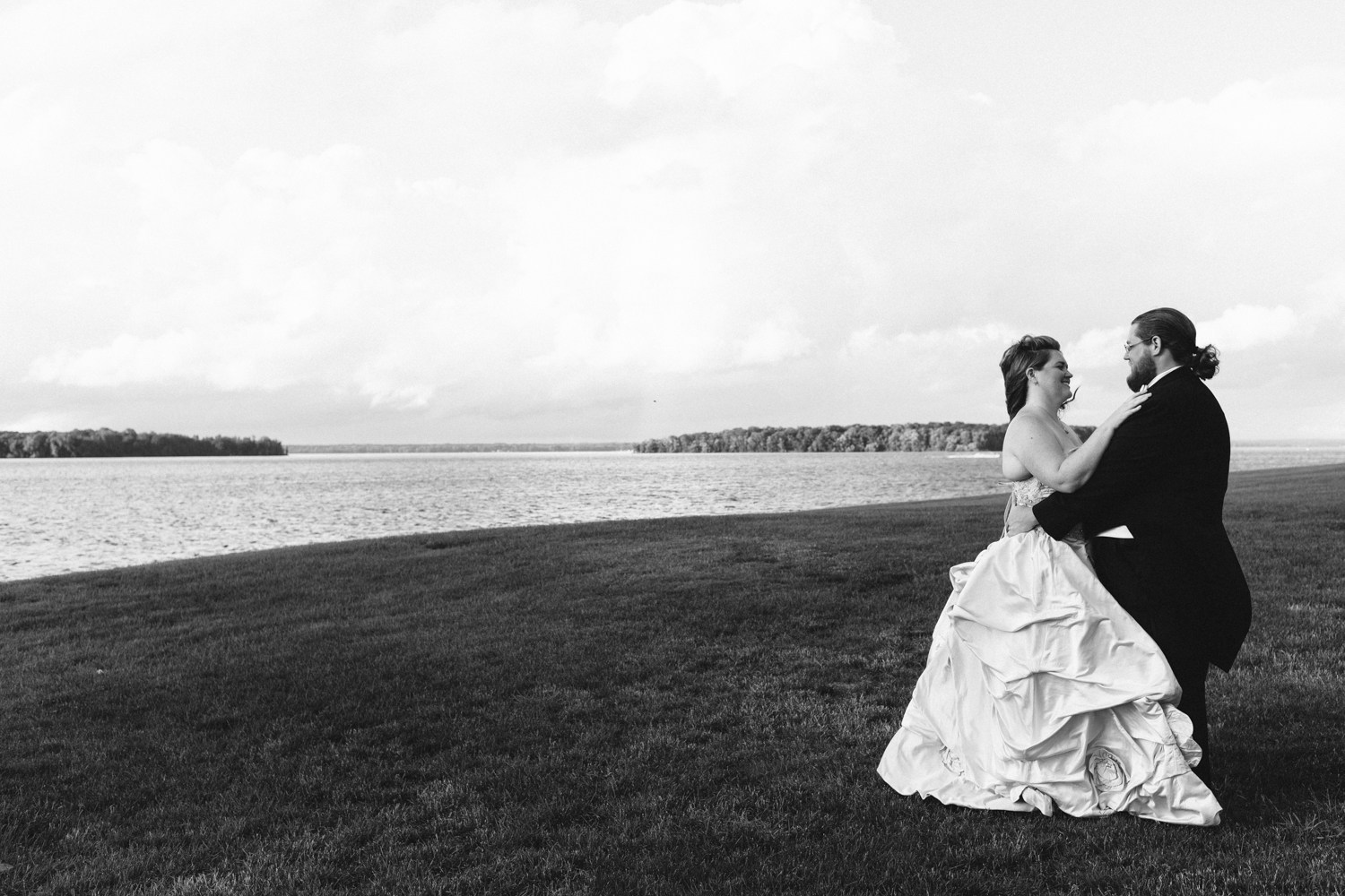 Black and white image of a bride and groom standing near a lake. Bride is wearing a ball gown.