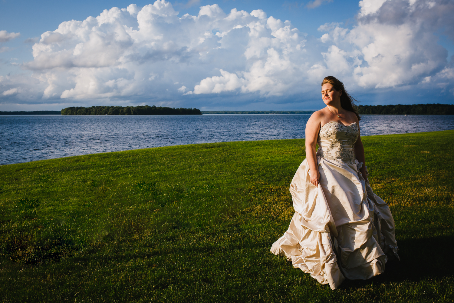 Bride smiles with eyes closed. She stands in front of a lake with fluffy white clouds behind her.