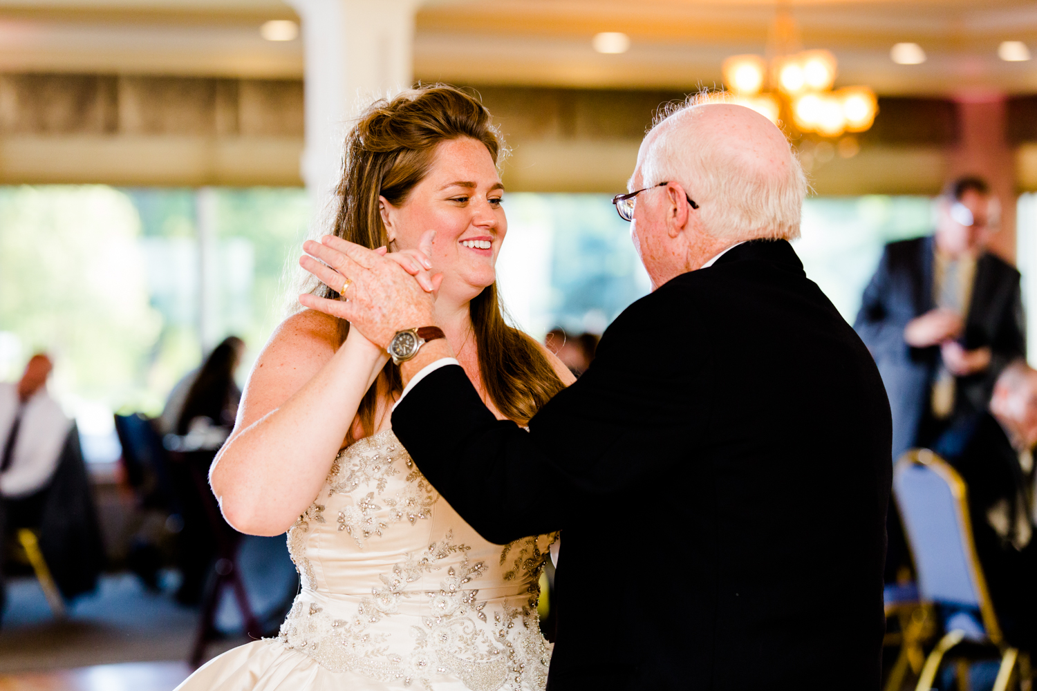 Bride smiles at her dad as they share a dance during her wedding reception.