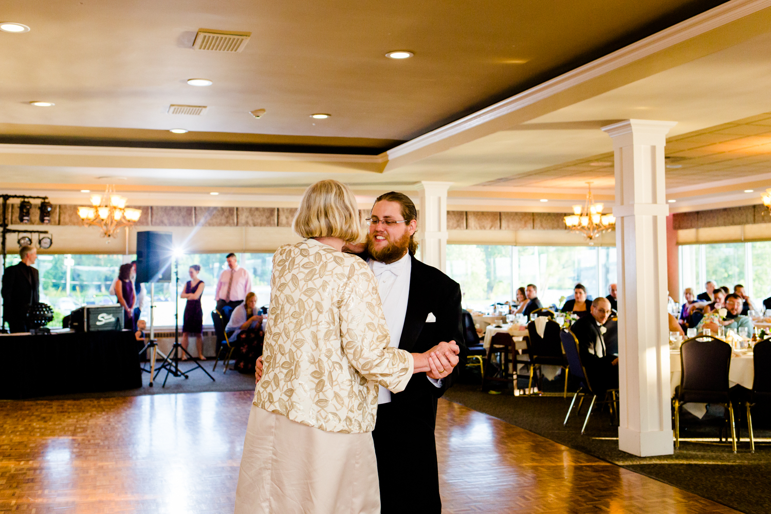 Groom smiles as he shares a dance with his mom.