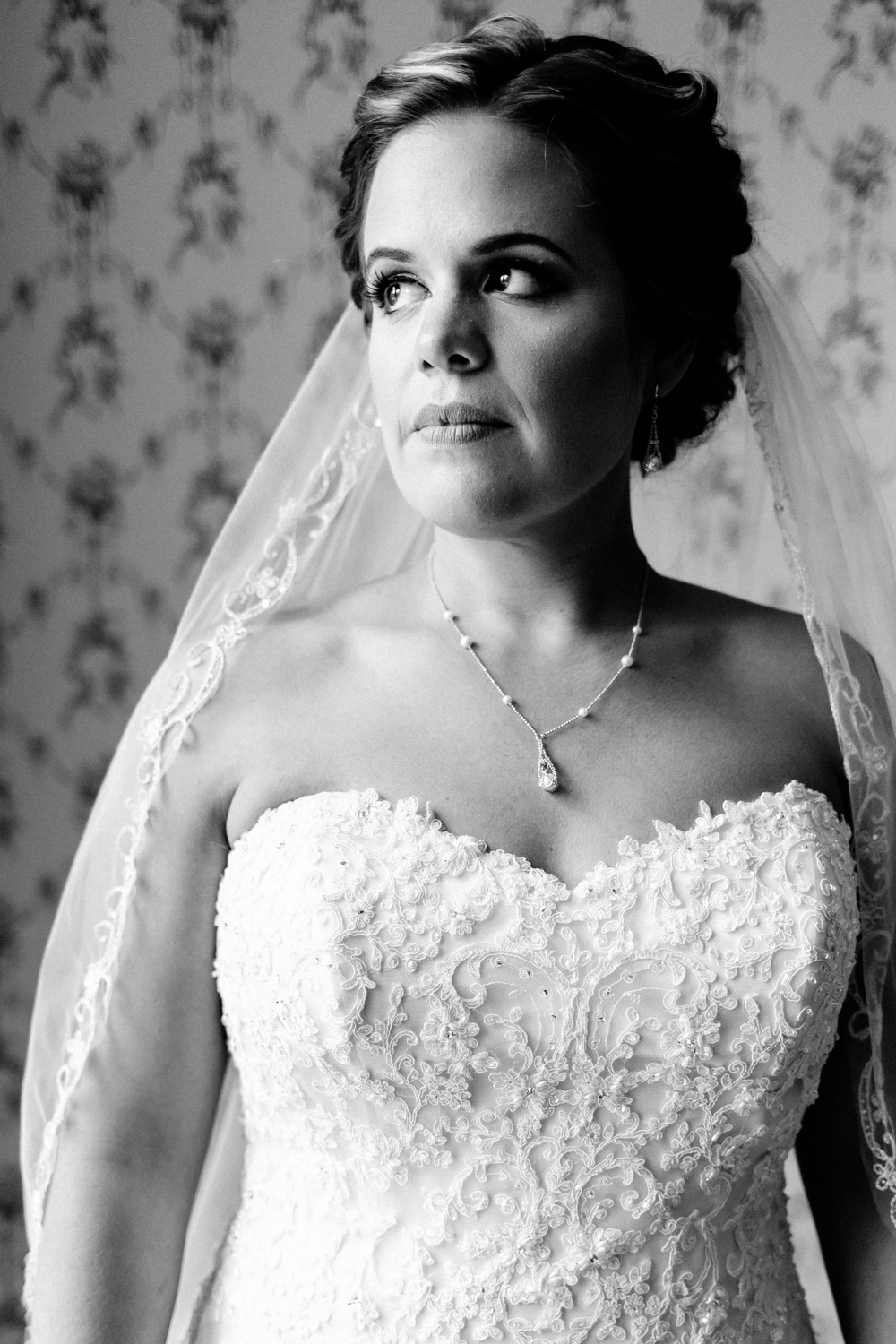 Black and white portrait of the bride in a sweetheart lace gown.