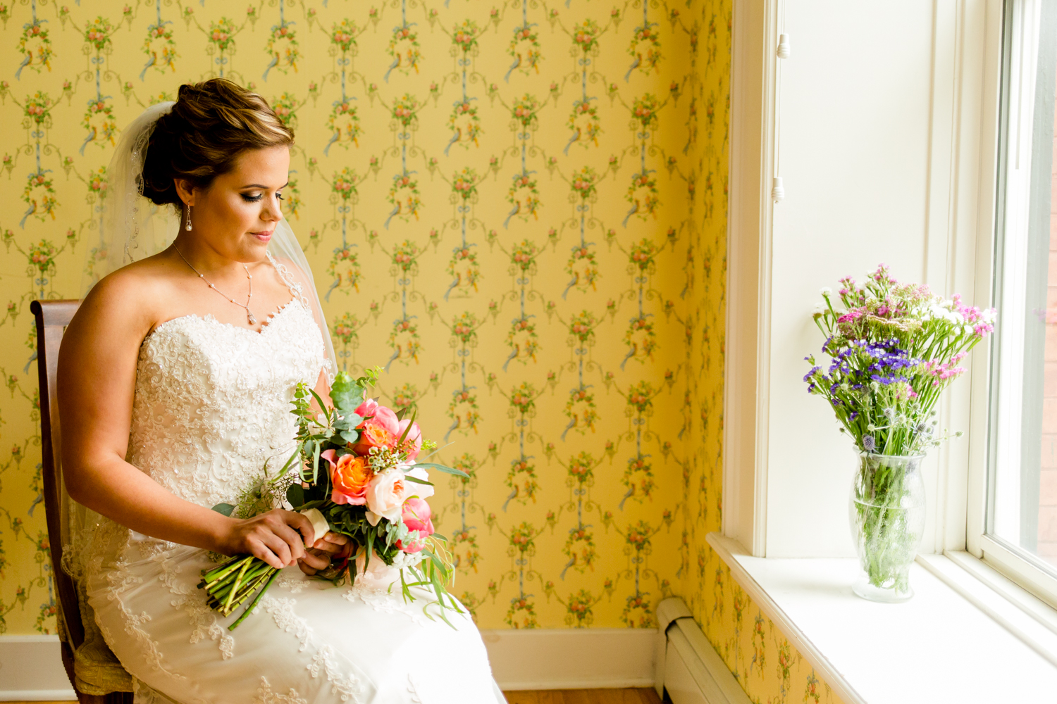 Bride sitting in front of vintage wallpaper holding flowers.