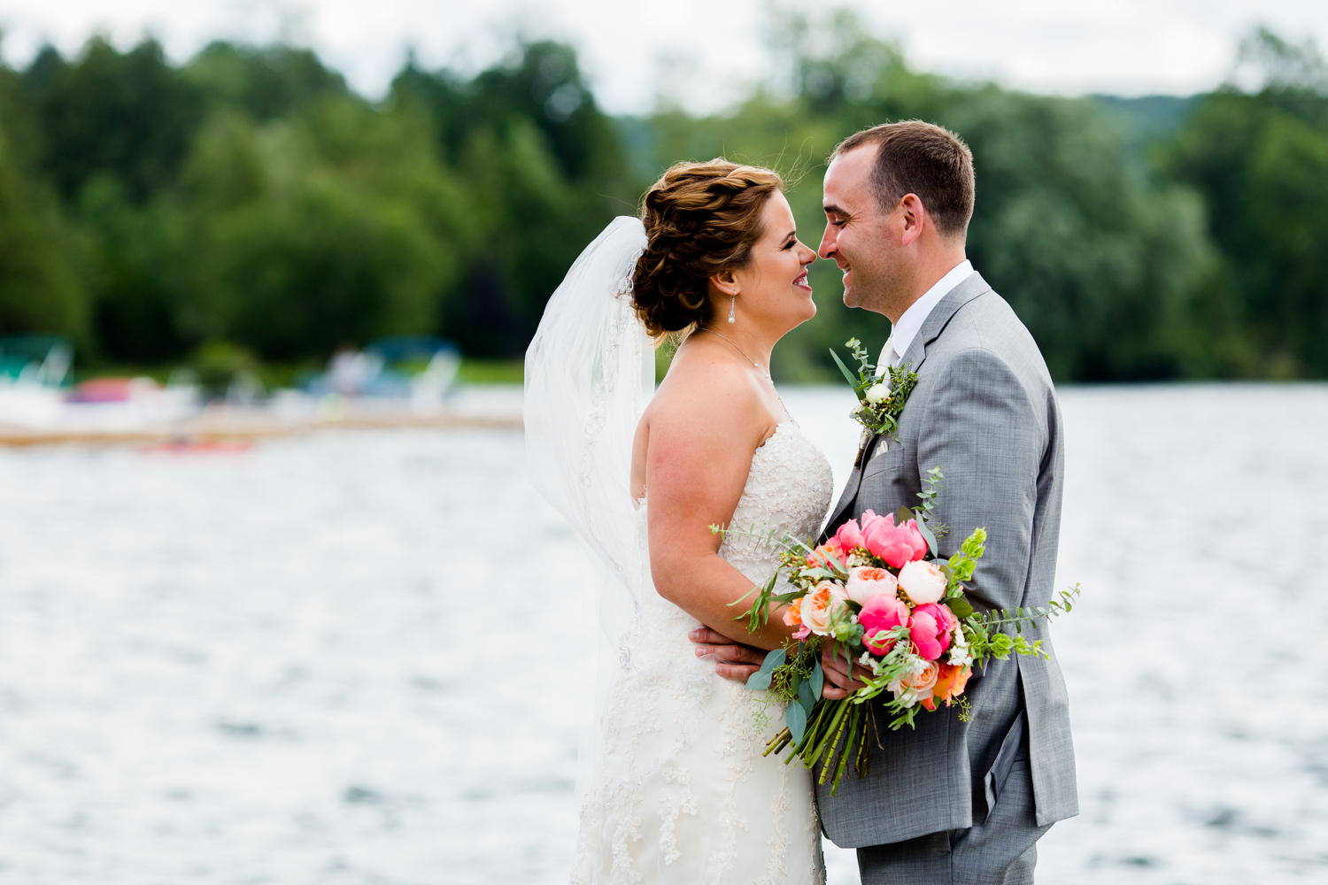 Bride and groom touch noses in front of a lake. Bride holds a bouquet of flowers.