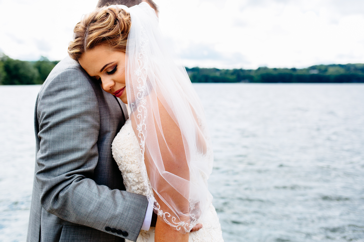 Bride rests her head on grooms shoulder. She wears a veil. They are in front of a lake.