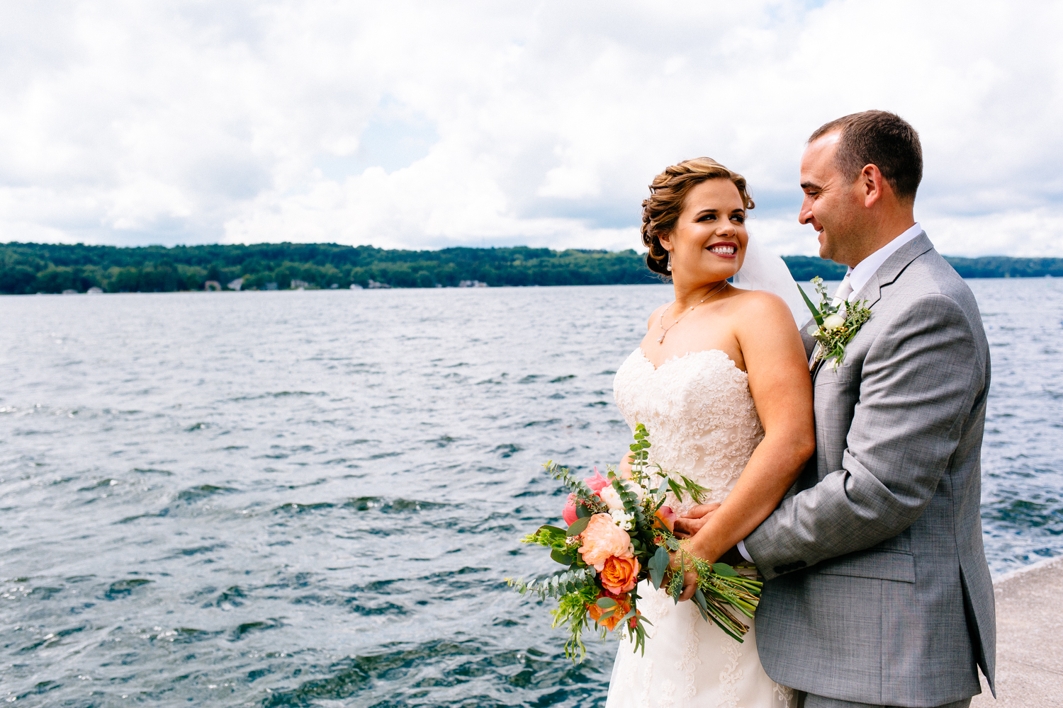 Bride and groom stand in front of Cazenovia Lake. Bride looks back at groom and smiles.