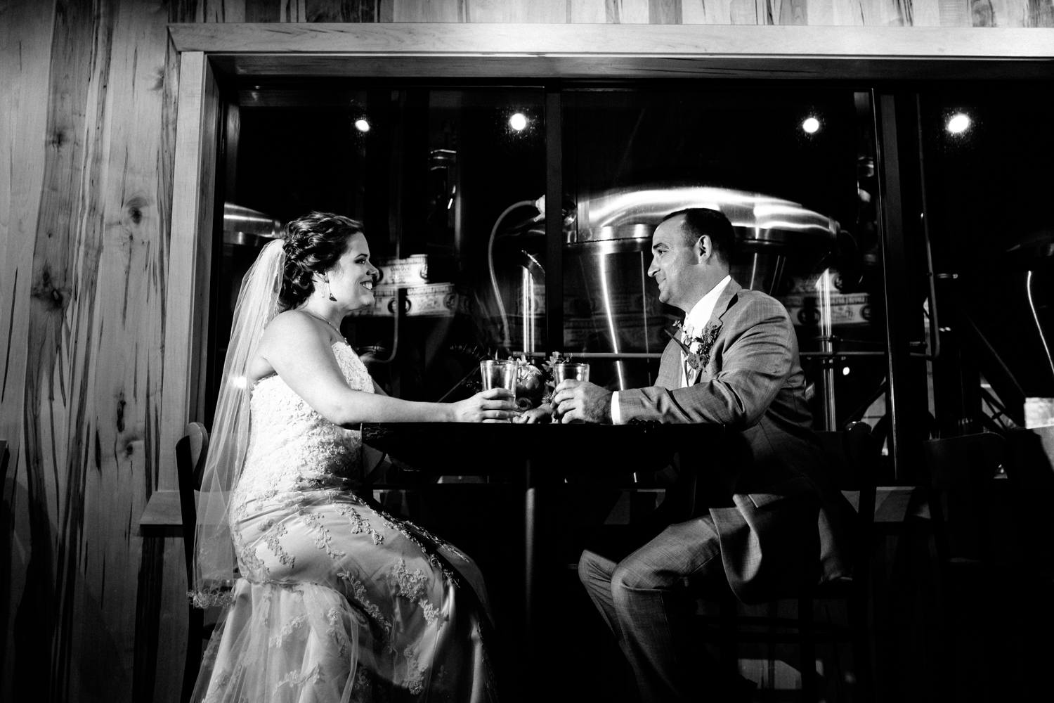 Black and white image of bride and groom having a beer at Empire Brewery in Cazenovia, NY.