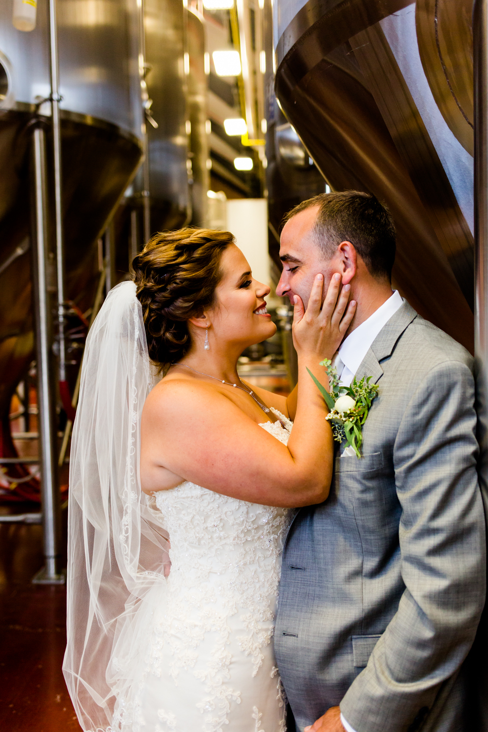 Bride holds grooms face in her hands.