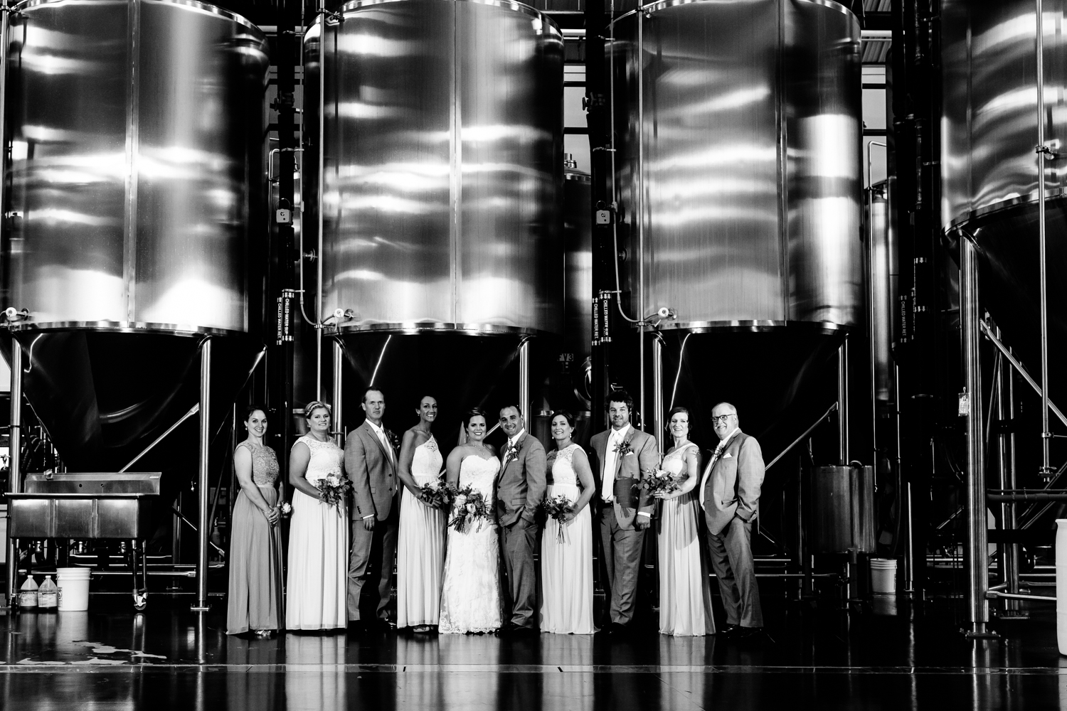 Black and white image of the bridal party in front of brewery equipment at Empire Brewery.