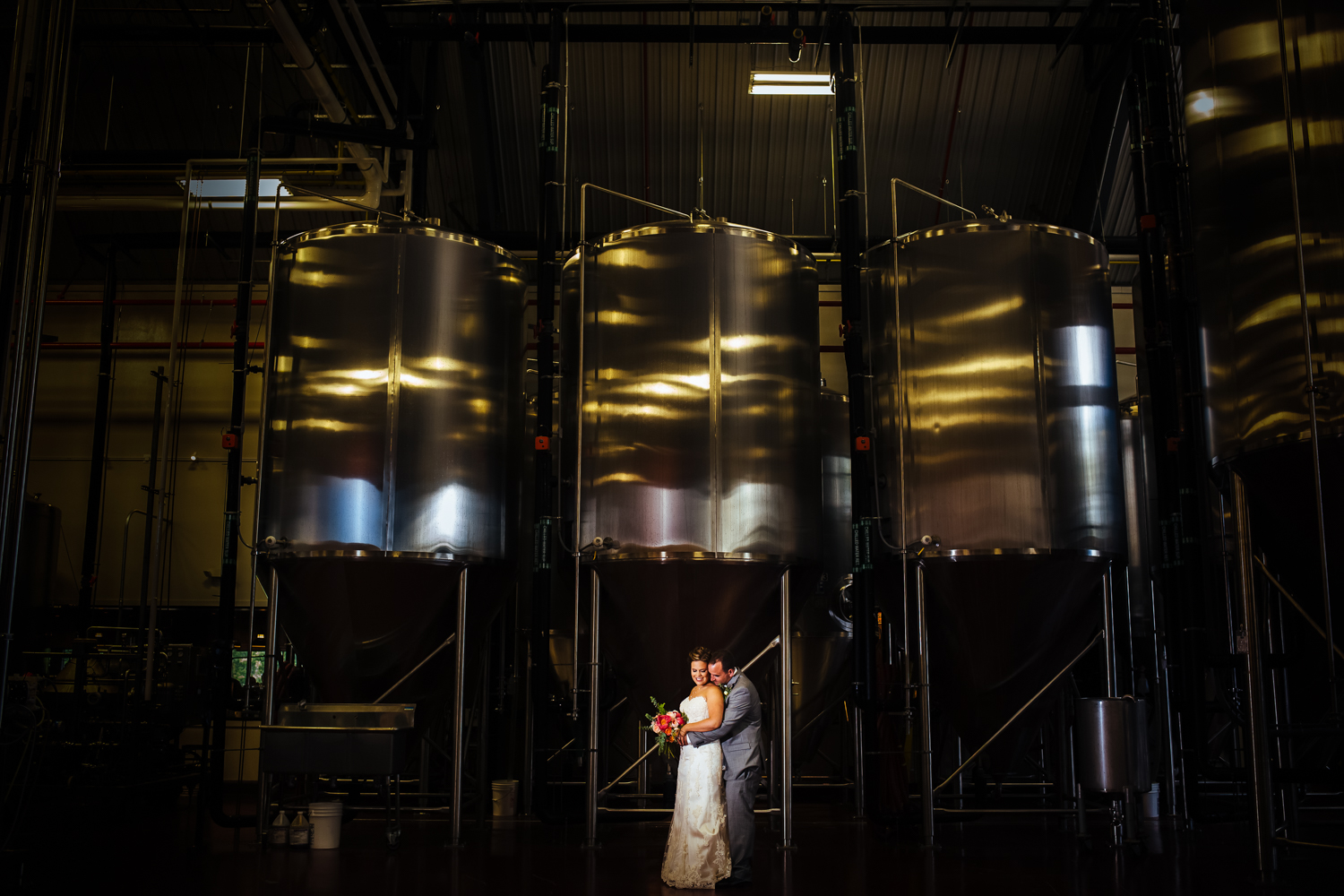 Dramatic photo of bride and groom in a brewery.