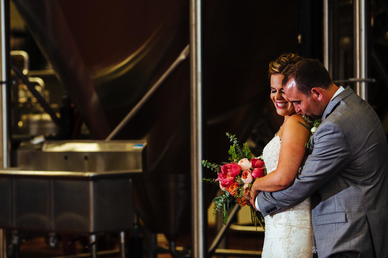 Groom kisses bride on shoulder while bride smiles.