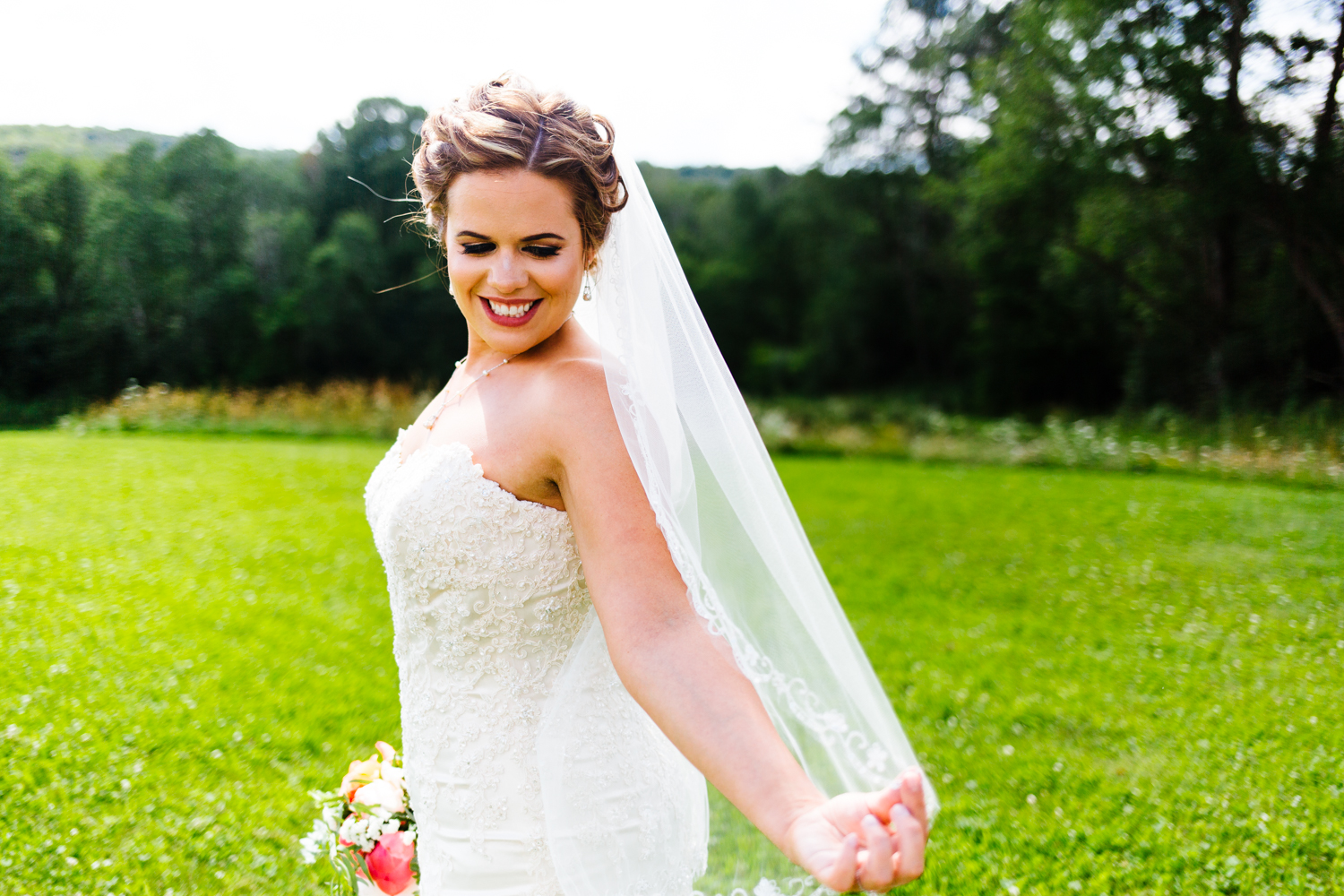 Bride holds out her veil and looks down at it. Trees line the background.