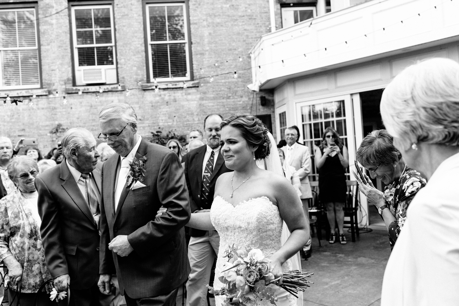 Black and white image of an emotional bride as she walks down the aisle with her father.