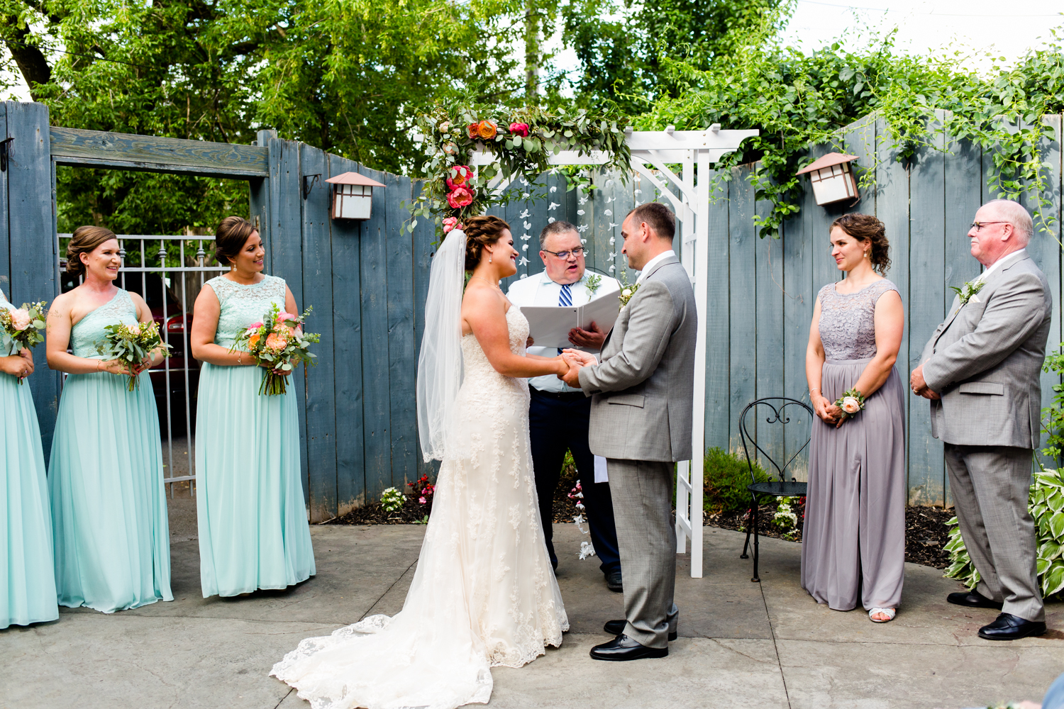 Bride and groom stand facing each other during the ceremony.
