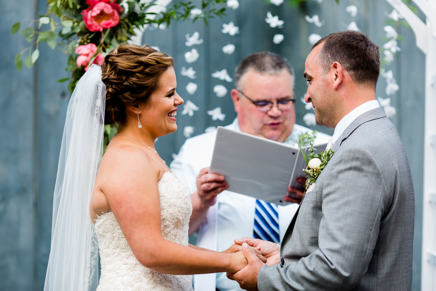 close up of bride and grooms happy faces during ceremony.