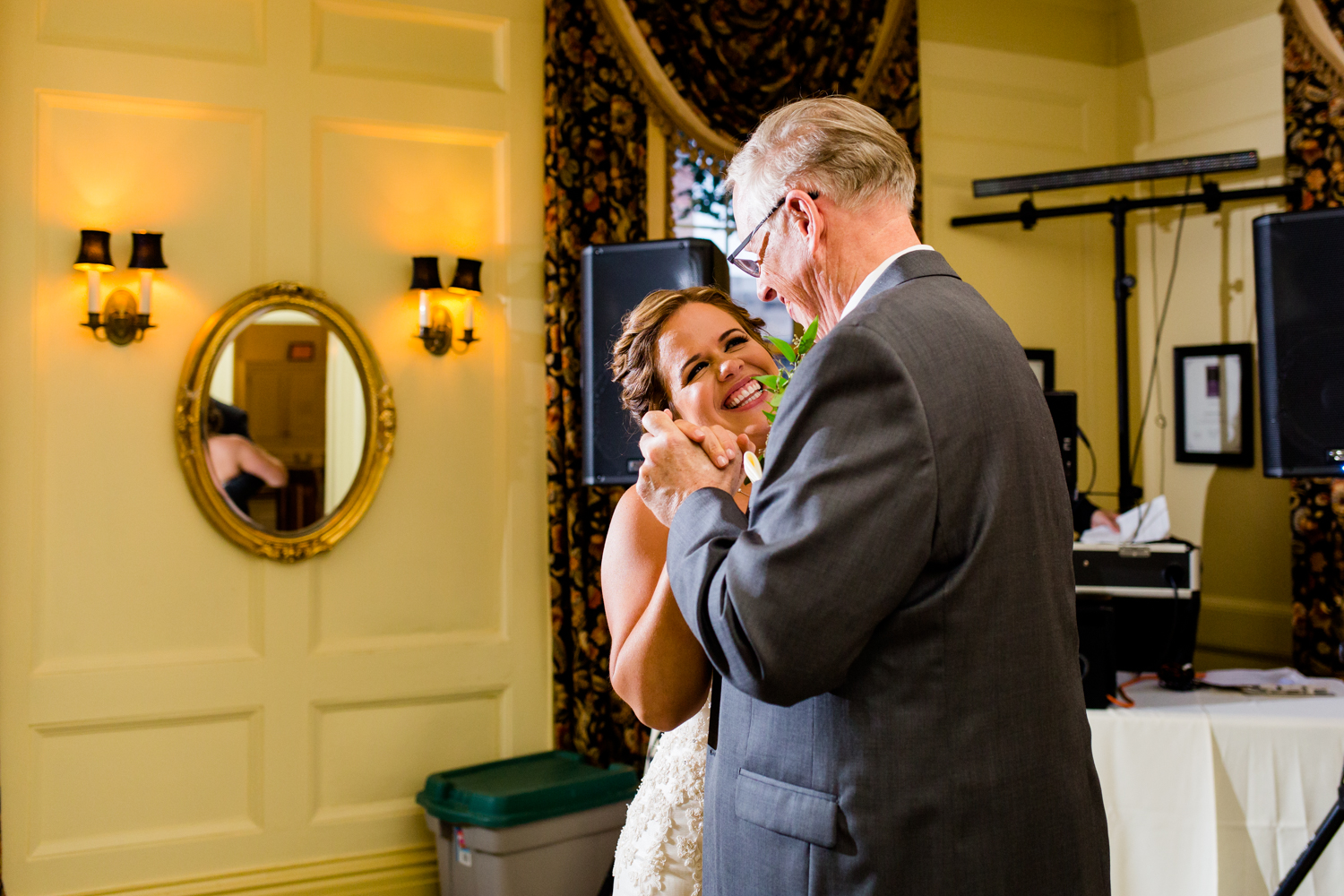 Bride smiles during father daughter dance.