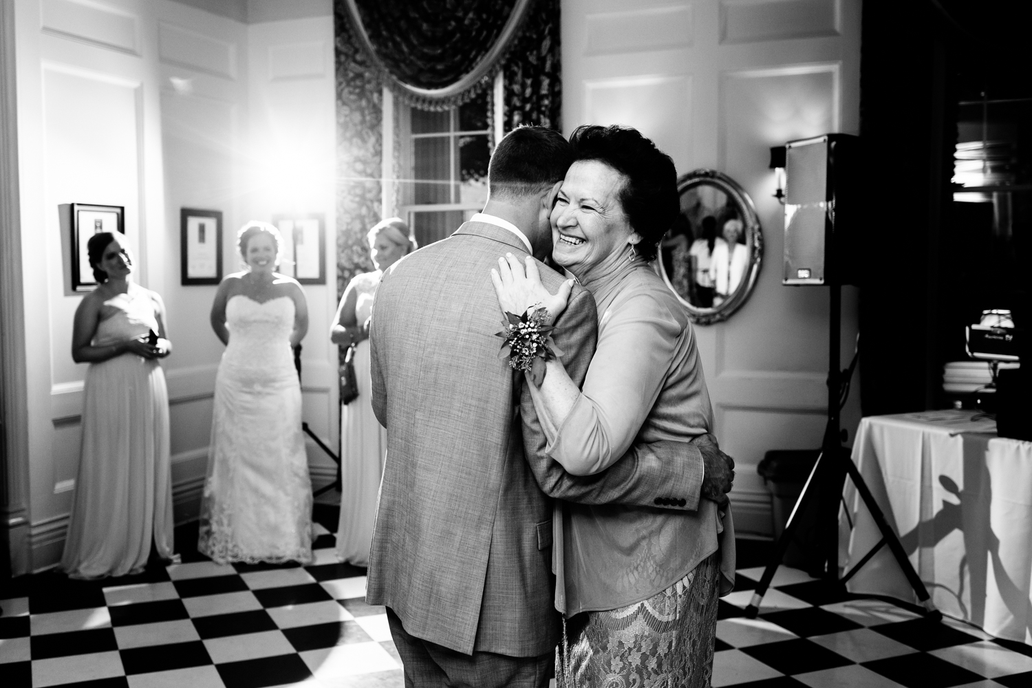 Black and white image of mother smiling during mother son dance at a wedding.