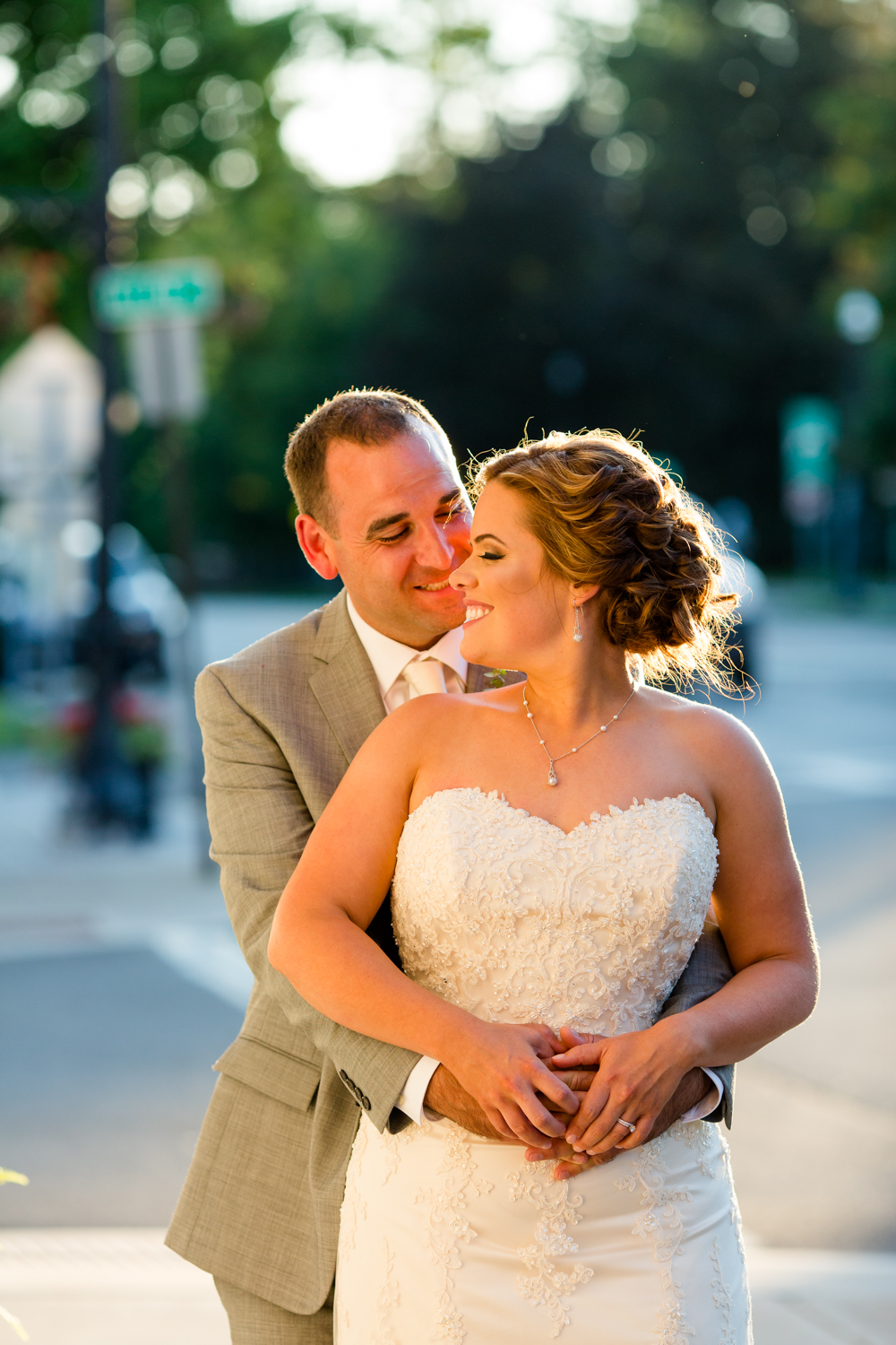 Sunset photo of groom holding bride around the waist. Bride is wearing a lace wedding gown.